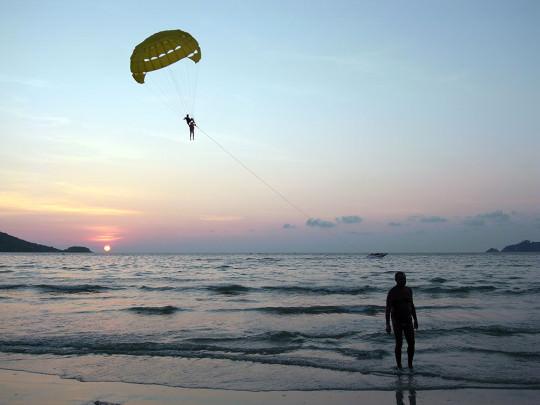 パトンビーチでグライダーを楽しむ観光客と夕暮れ